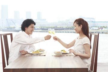 ダイニングテーブルで乾杯するカップル