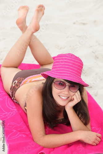 Young woman lying on a pink beach towel
