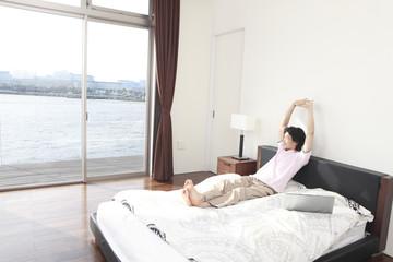 ベッド上でのびをする男性
