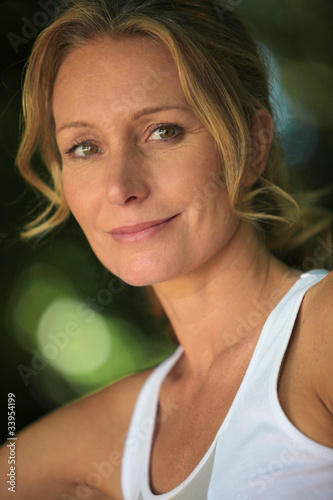 Closeup of woman in white vest in leafy environment