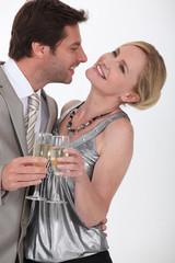 Flirtatious man and woman drinking champagne