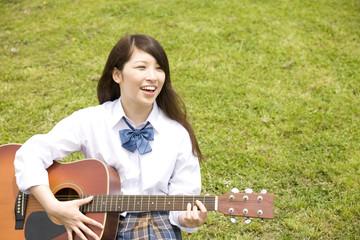 丘に座りギターを弾く女子高生