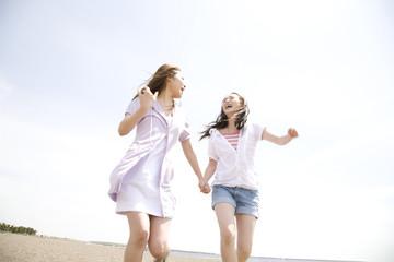 砂浜を走る2人の女性