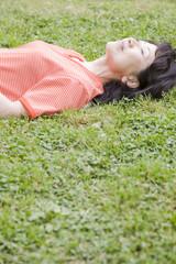公園の芝生に仰向けに寝転がる女性