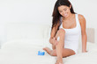 cute woman putting cream on her legs