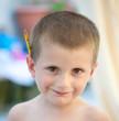 Enfant de 4 ans, blond, avec un crayon derrière l'oreille.