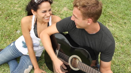 Cute young couple in the park with acoustic guitar