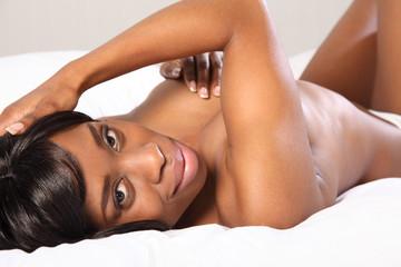 Happy beautiful black woman topless in bedroom