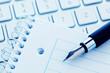 Notizblock und Tastatur eines Computers