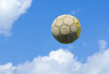 An old soccer (football) ball flies in a blue cloudy sky.