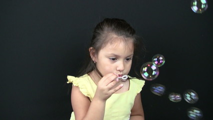 Child blowing bubbles closeup