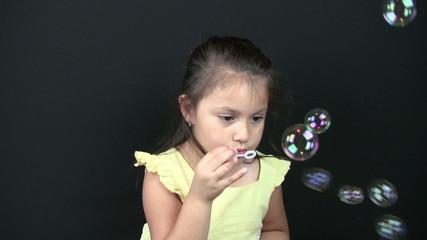 Child blowing bubbles closeup