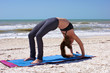 woman doing yoga exercise full wheel pose on beach