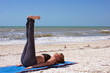 woman doing yoga exercise reclined staff pose on beach