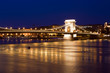 Budapest skyline, reflected on the river bridge at night.
