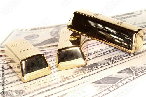 drei große Goldbarren auf Dollarnoten