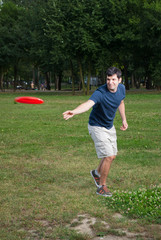 young man playing frisbee outdoors