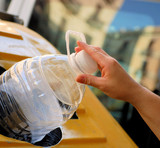 female hand throwing out a plastic large bottle in container for