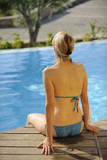 Rear view of woman tanning at poolside poster