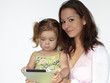 Mother and adorable little girl having fun with touchpad
