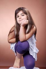 Kleines Mädchen kniet und blickt cool