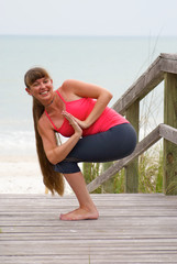 happy woman doing yoga exercise rotated awkward chair pose