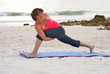woman on beach at sunset doing yoga exercise side angle
