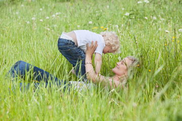 Mother lying on grass and playing with son