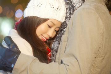 クリスマスイルミネーションバックに抱き合うカップル