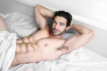 Sexy męski model uśmiech w łóżku