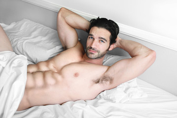 Sexy male model smile in bed
