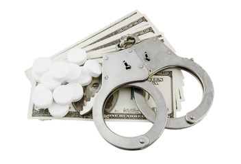 Steel metallic handcuffs, money and tablets isolated