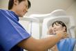 歯のレントゲンを撮られる女性