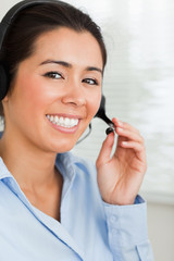 Portrait of a good looking woman with a headset helping customer