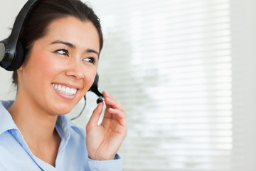 Portrait of a pretty woman with a headset helping customers whil