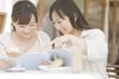 オープンカフェで雑誌を読む2人の女性