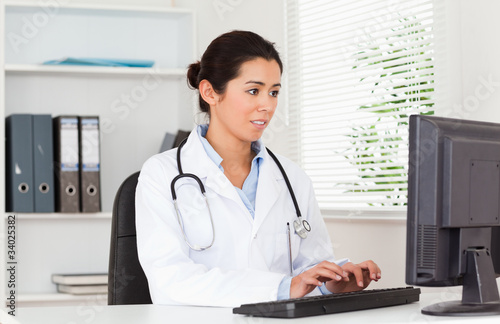 Georgeous female doctor typing on a keyboard while sitting