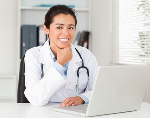 Attractive female doctor working with her laptop while posing