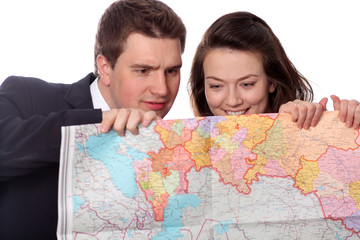 Closeup of a happy casual couple with map isolated on the white