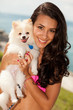 Pretty young brunette woman with her Pomeranian puppy
