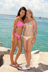 Pretty young blond and brunette girls enjoying the beach