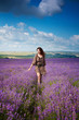 Young beautiful girl in the brown dress in lavender field