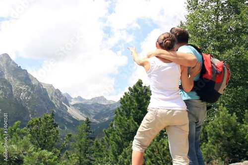Couple in the mountains looking at beautiful landscape