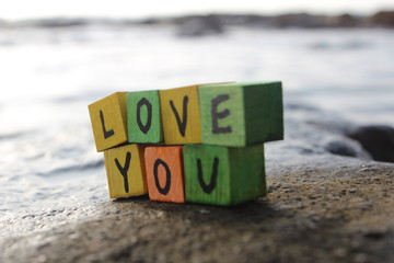 Love you - written on wood cubes, on the beach