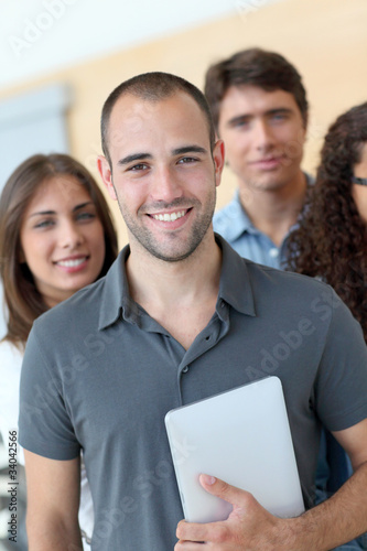 Portrait of student standing with workgroup