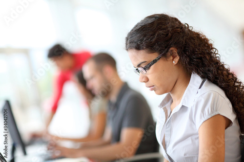 Portrait of smiling student in front of laptop computer