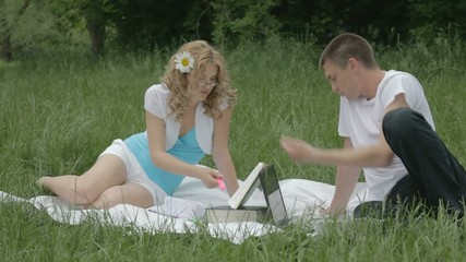 Young couple disputing with opened book and laptop on grass