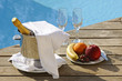 Champagne at poolside with plate of fruits and glasses