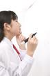 ホワイトボードに書かれた問題の答えを考える女子中学生
