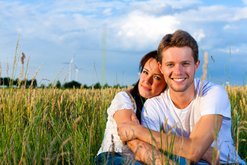 Happy couple sitting on a meadow or grainfield